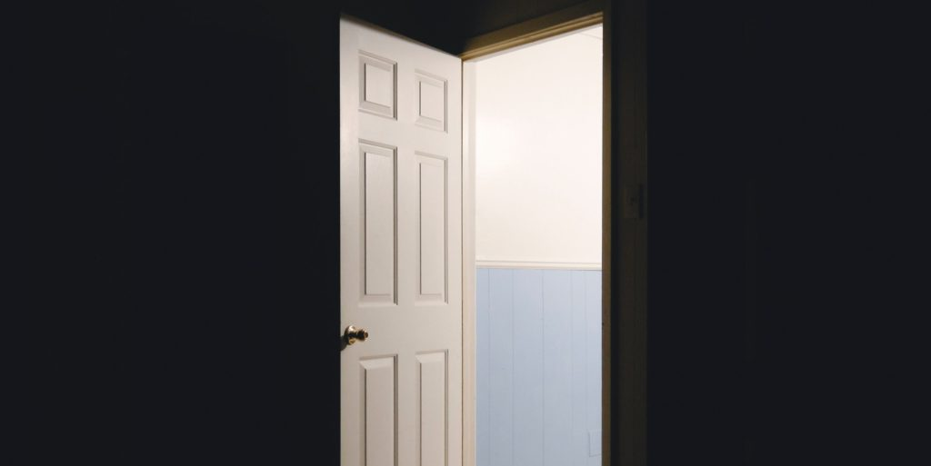 An open door allowing light to shine into a dark room.