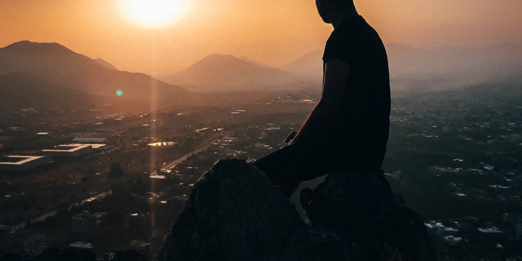 Man sitting on rock during golden hour