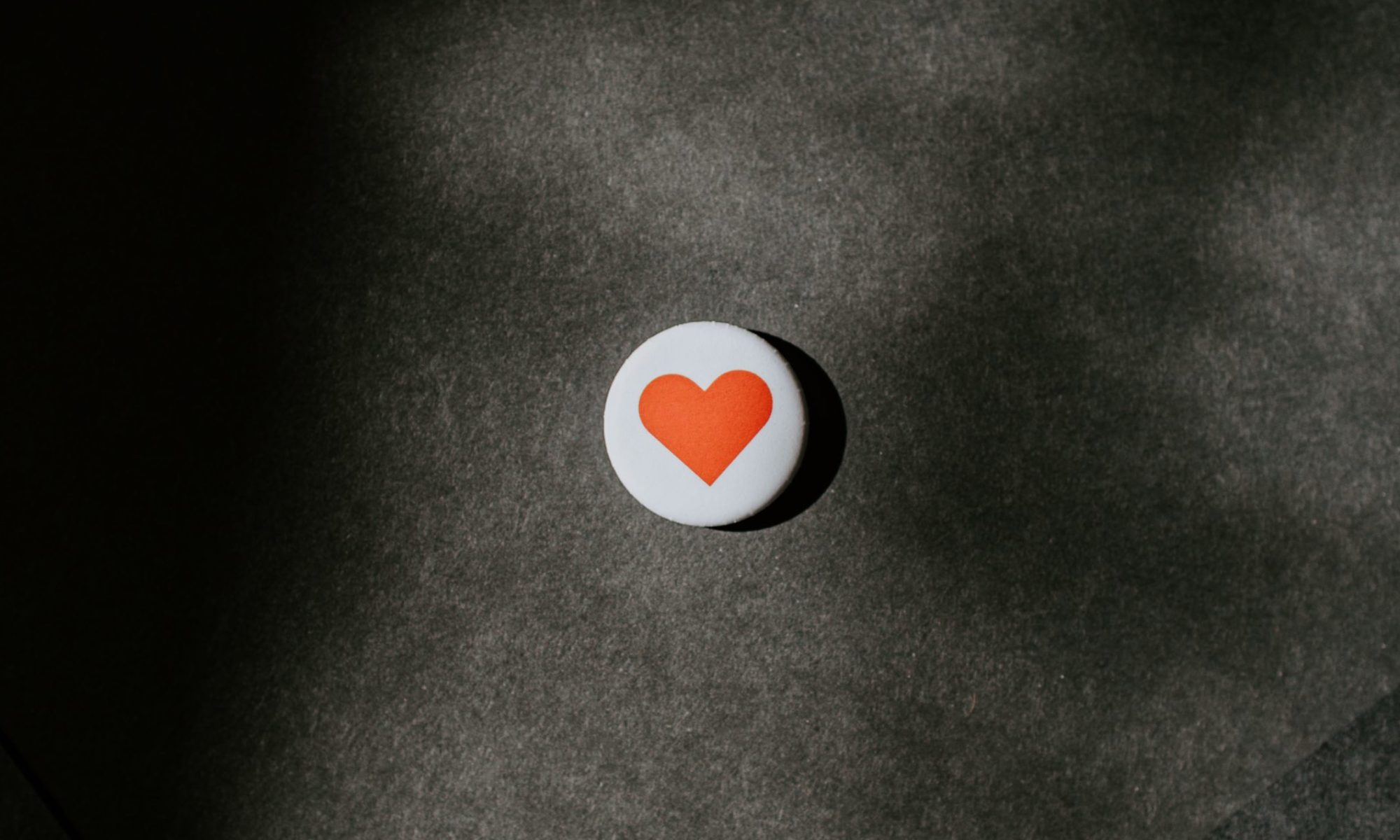 Pin button in the sun on black paper