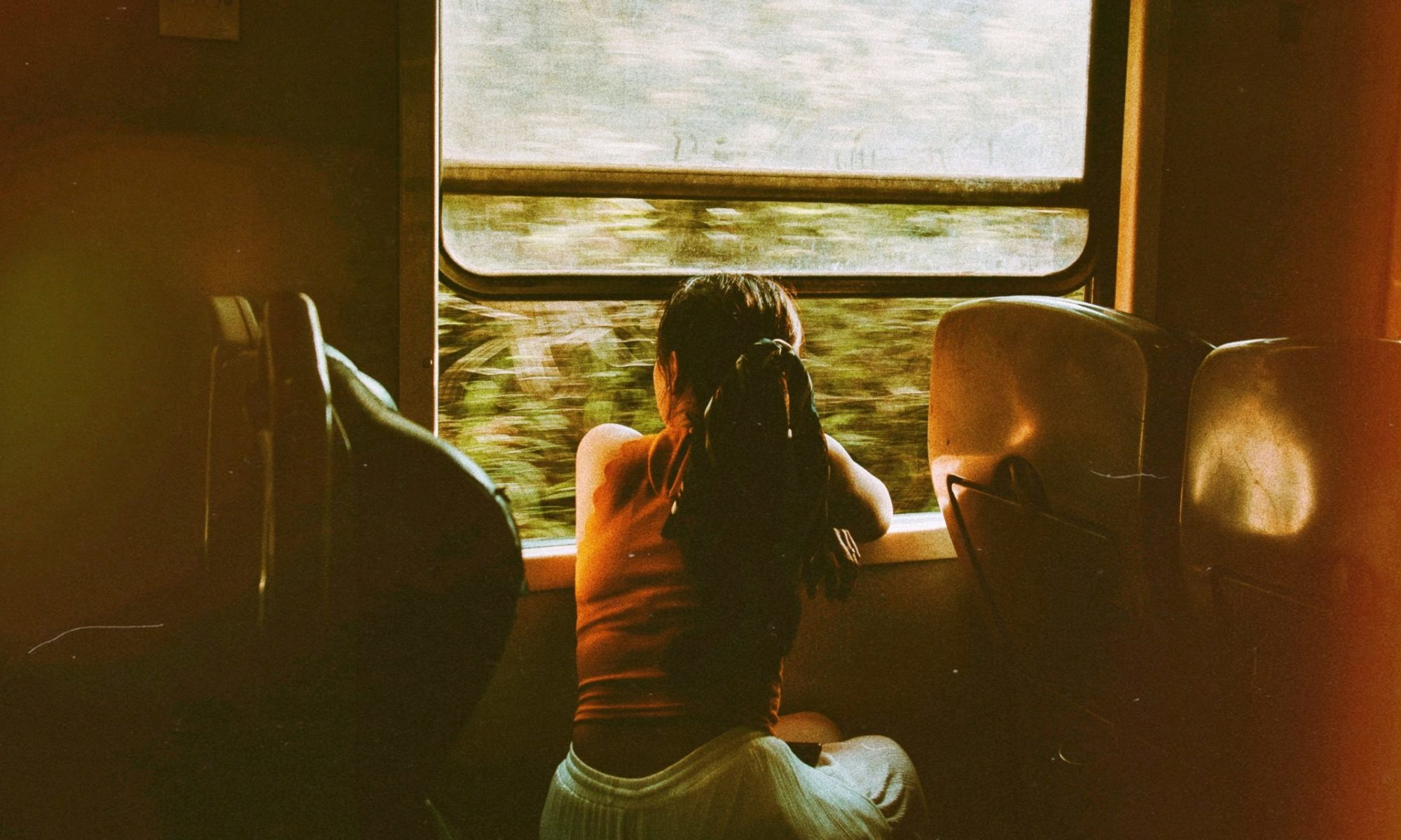 Unrecognizable woman riding train and looking out window